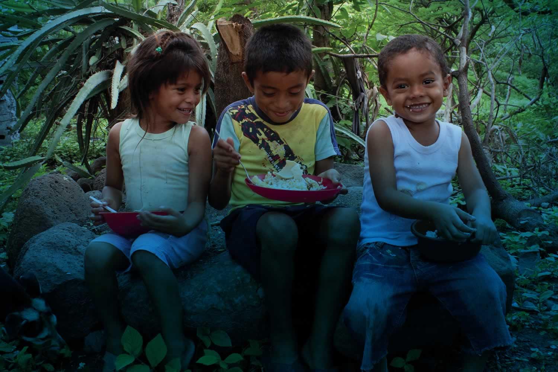 Three young children sitting on rocks