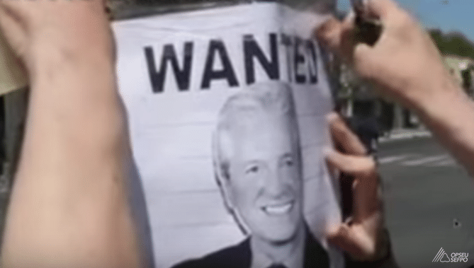 Two arms put up a poster on a hydro pole. Poster says WANTED over a photo of MPP Mike Cole.