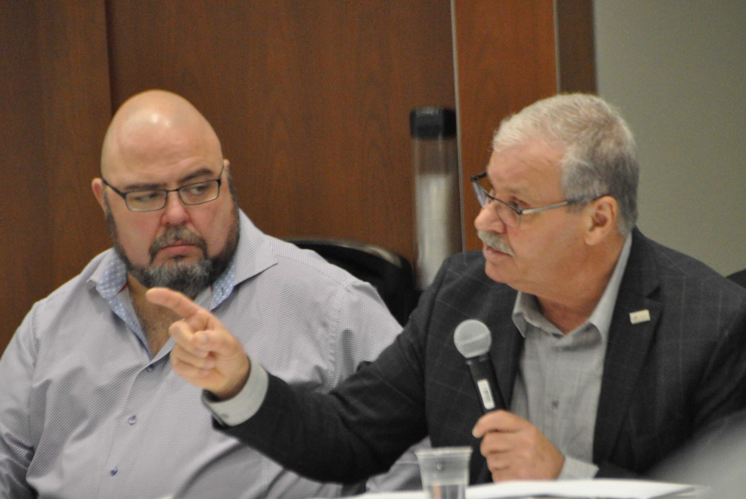 OPSEU President Warren (Smokey) Thomas speaks into a microphone and gestures during the Ford government's public sector consultations.