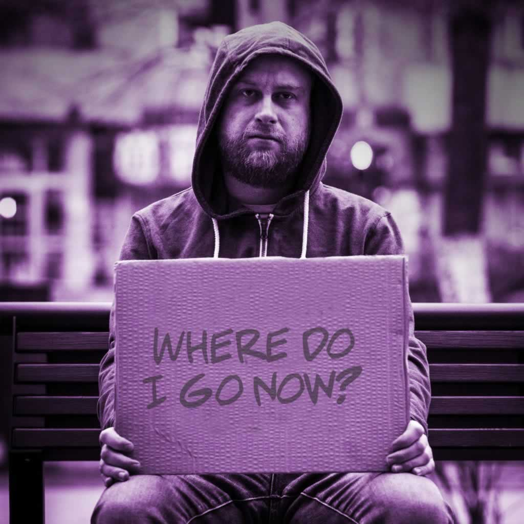 "Homeless person sitting on a bench holding a sign that says ""Where do I go now?"""