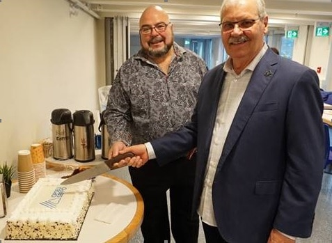OPSEU President Warren (Smokey) Thomas and First Vice-President/Treasurer Eduardo (Eddy) Almeida cut a cake with the OPSEU logo on it.