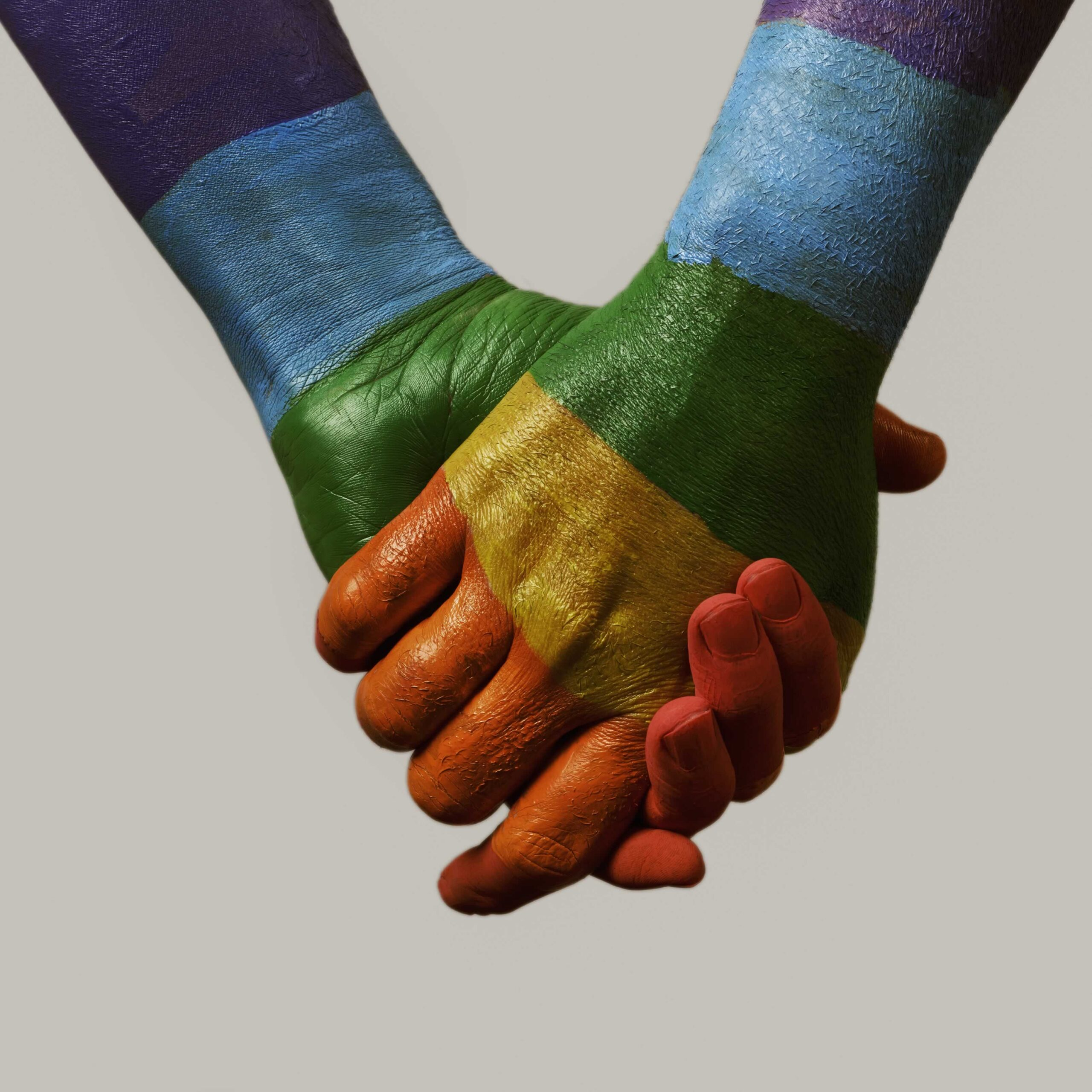 Arms of two people holding hands panted in the colours of the pride flag.