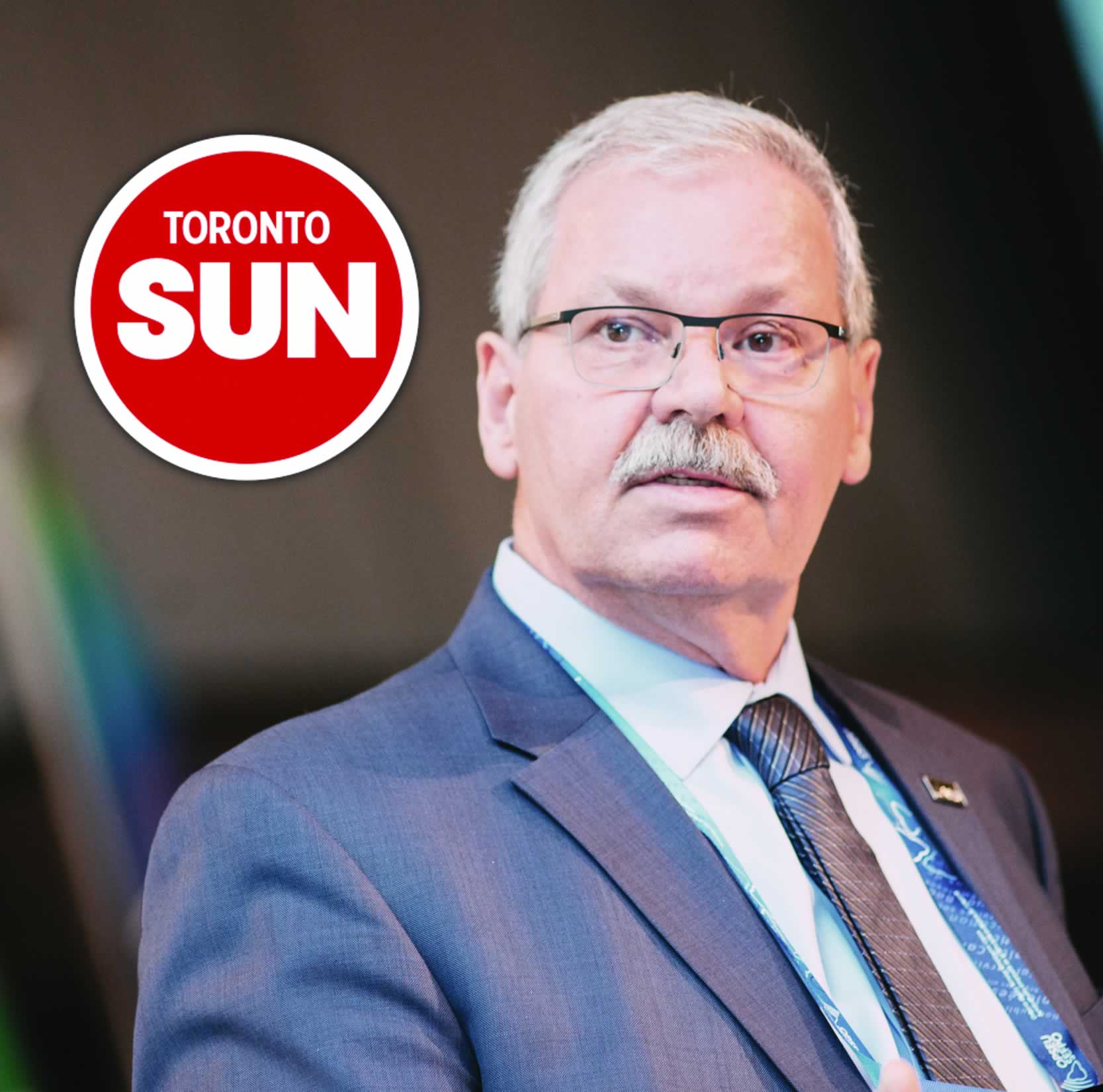 OPSEU President Warren (Smokey) Thomas with a Toronto Sun logo.