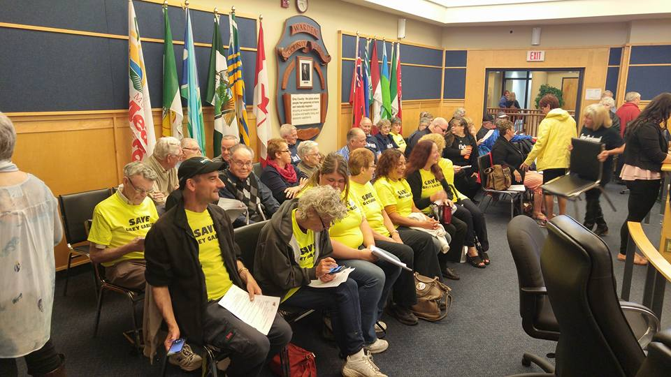 "People wearing yellow ""Save Grey Gables"" shirts pack a meeting room."