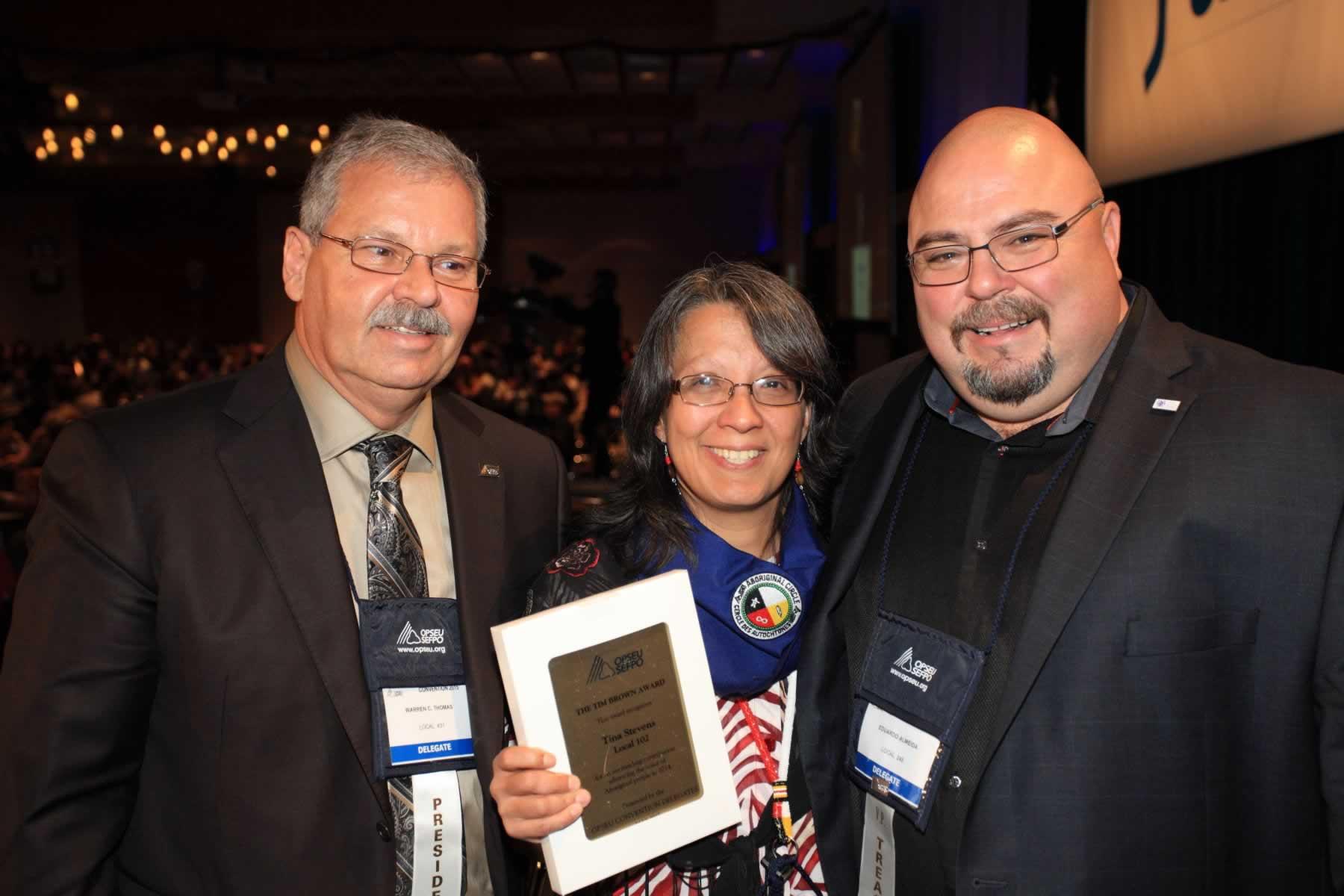 OPSEU President Warren (Smokey) Thomas and First Vice-President/Treasurer Eduardo (Eddy) Almeida with Tim Brown Award winner Tina Stevens during Convention 2015