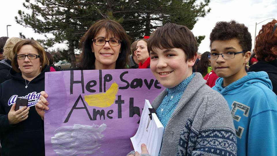 "NDP MPP Theresa Armstrong holding a sign that says ""Help Save Amethyst"" at a rally with students"