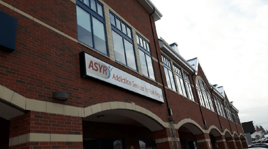 Front of a long, low brick building with a sign saying ASYR over the front entrance