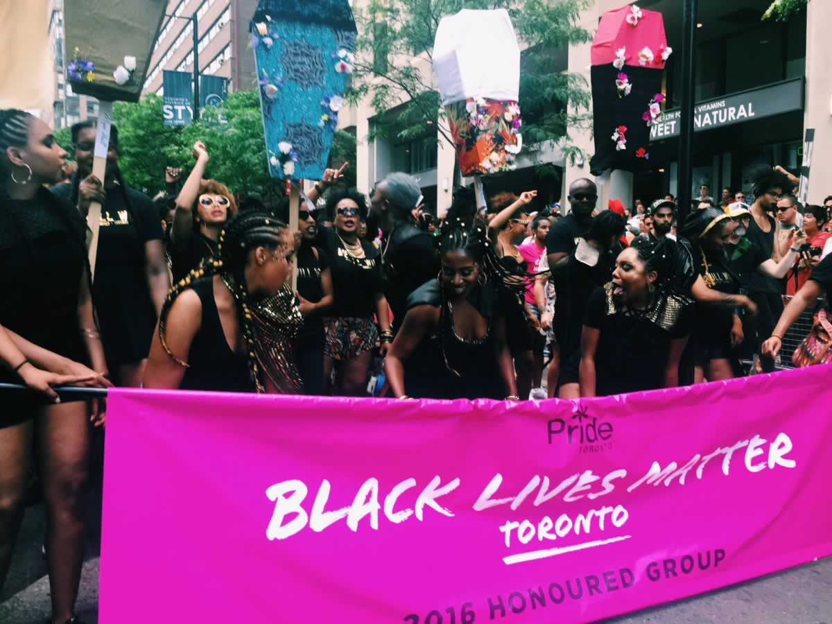 """Large group of Black people and allies march with a """"Black Lives Matter Toronto"""" banner during the Toronto Pride Parade."""