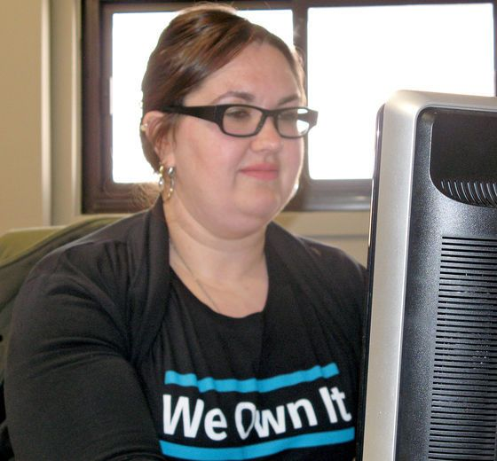 OPSEU member wearing We Own It shirt at a computer.
