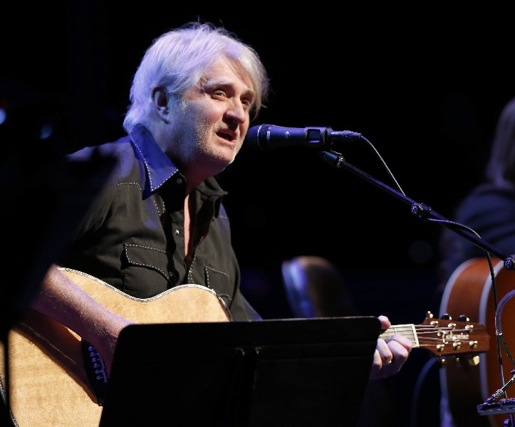 Tom Cochrane plays guitar and signs in to a microphone.