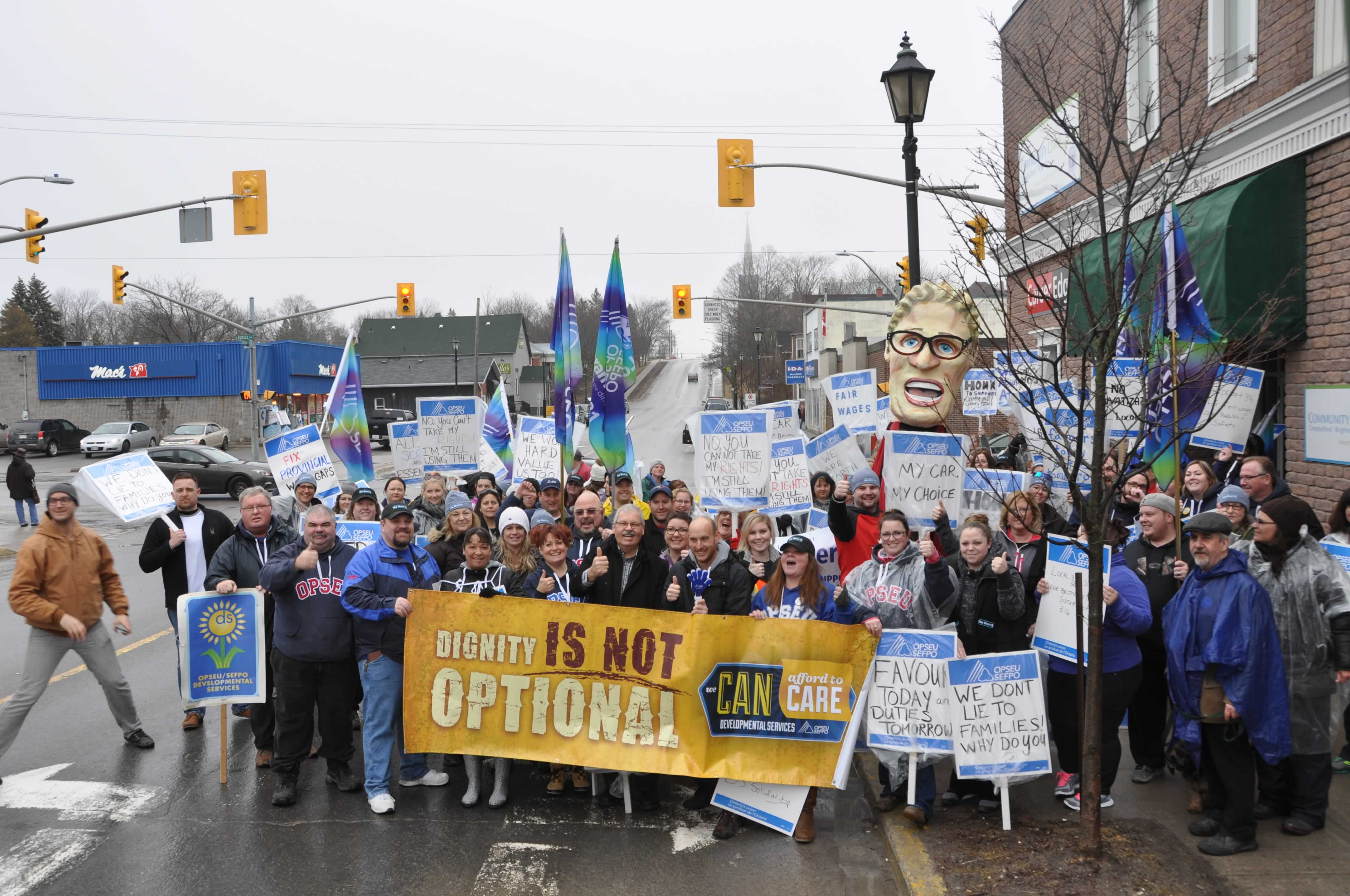 Large group of OPSEU members holding picket signs, flags, and banners during a rally in Campbellford.
