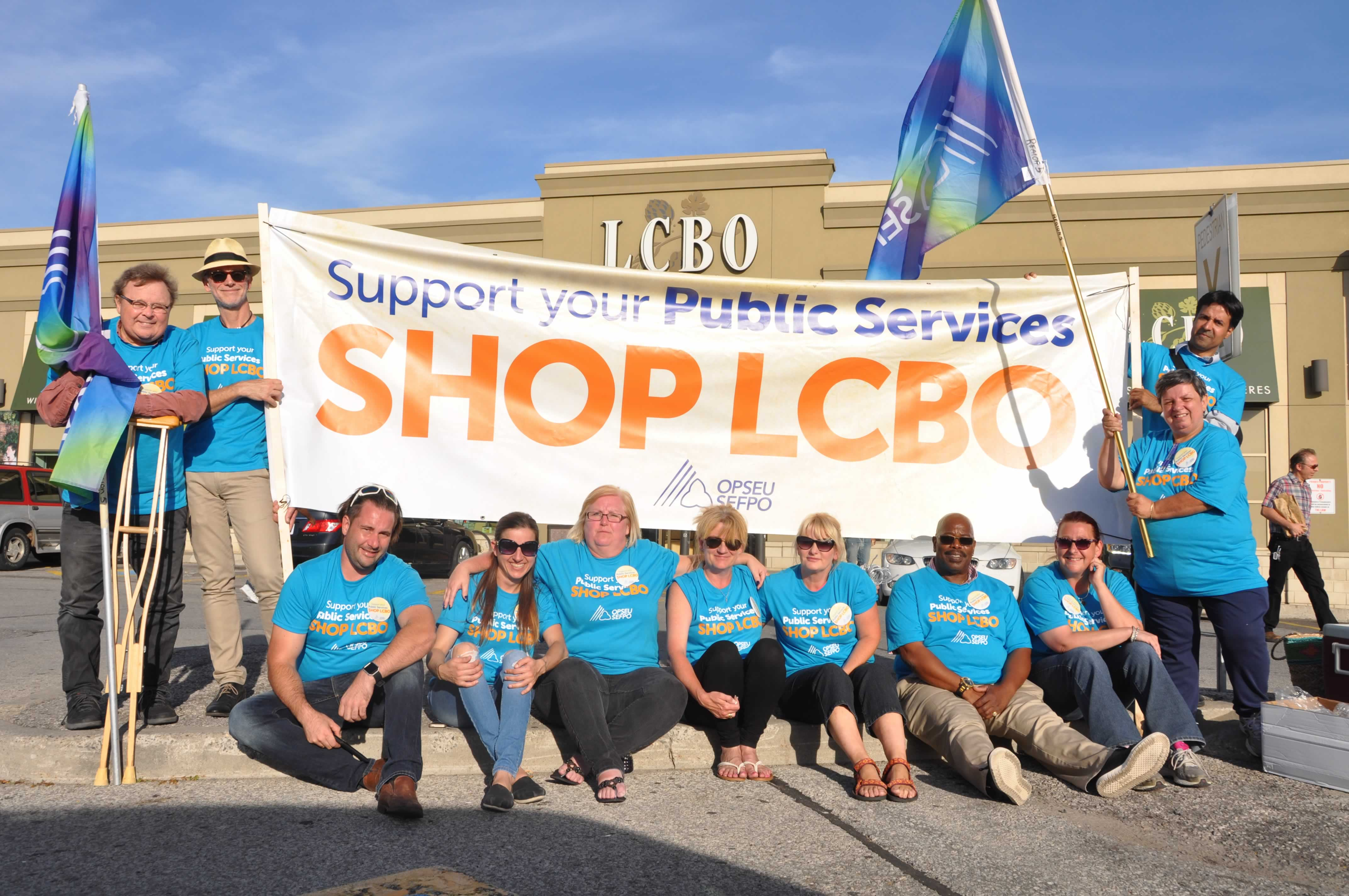 "Group of OPSEU members wearing blue shorts with a large banner that says ""Support your Public Services: Shop LCBO"""