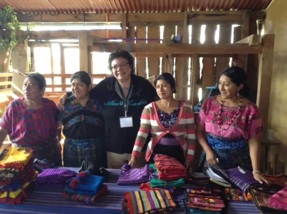 OPSEU member poses with women at a clothing market table in Guatemala.