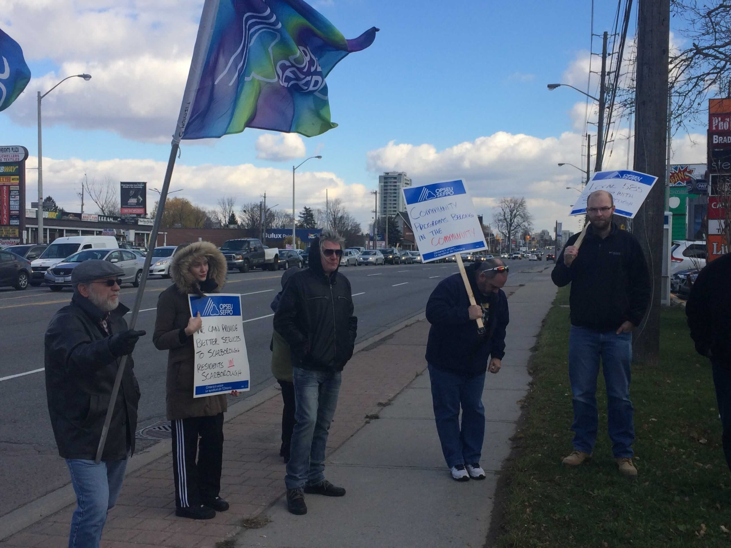 OPSEU members holding picket signs and flags rally in front of MPP Brad Duguid's office.