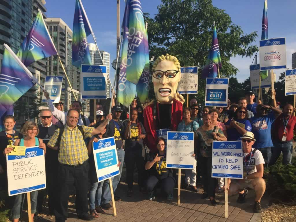OPSEU members rally at Pan-Am Games event with Kathleen Wynne puppet.