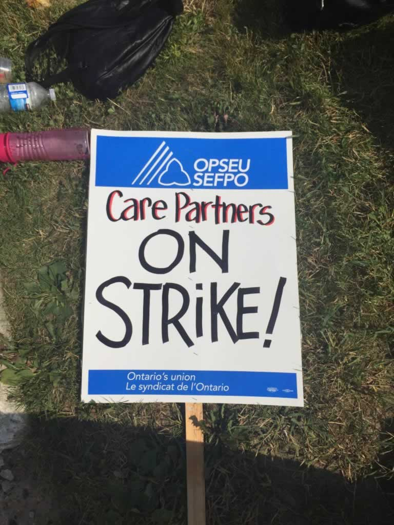 "OPSEU ""Care Partners On Strike!"" picket sign."