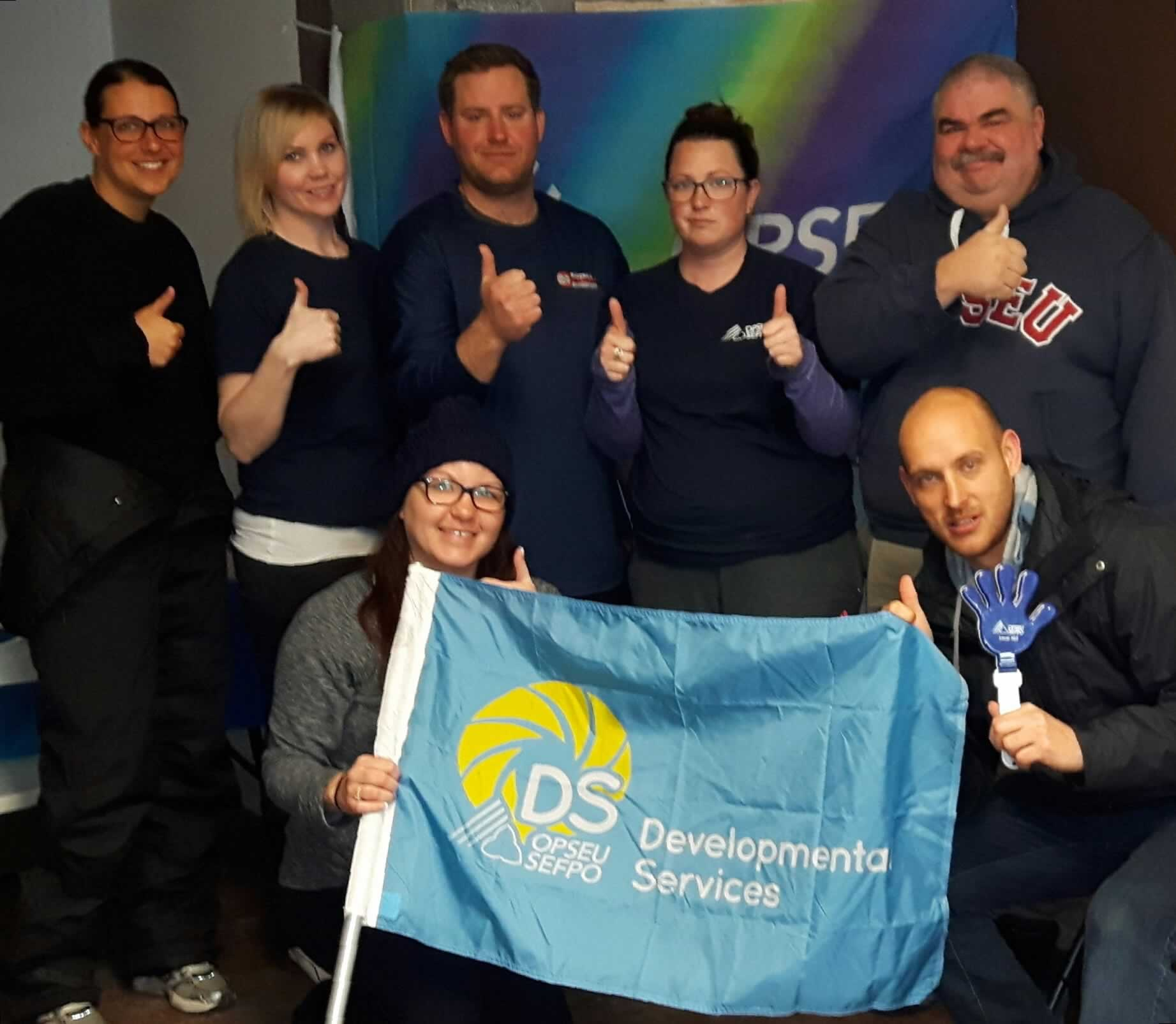 Members of the Local 316 bargaining team hold OPSEU Developmental Services flag and give thumbs-up.
