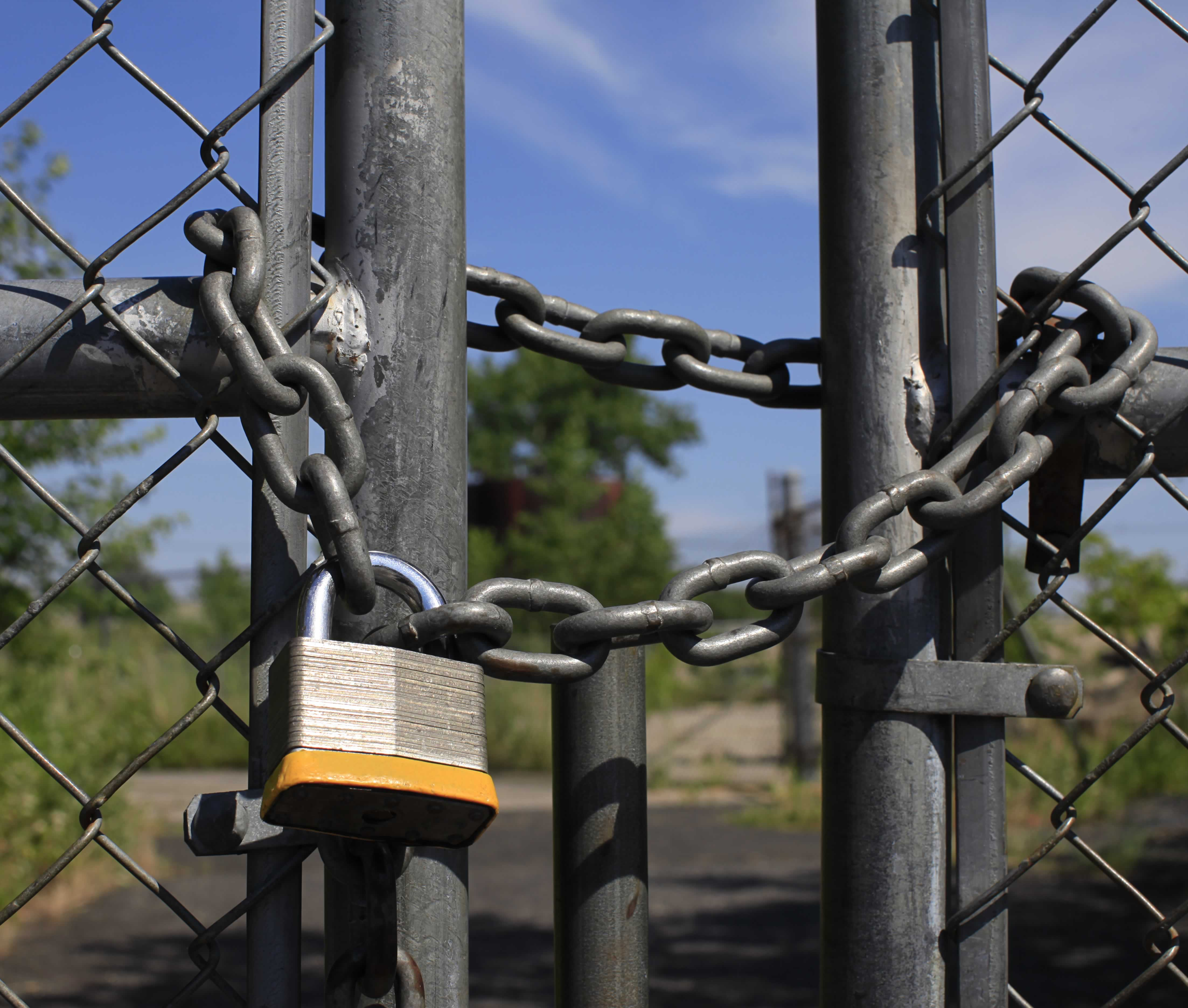 The gate to a chain-link fence is locked with a chain and padlock