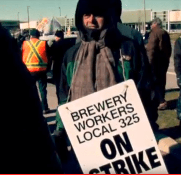 "Striker at Molson Coors holding a picket sign that says ""Brewery Workers Local 325 On Strike"""