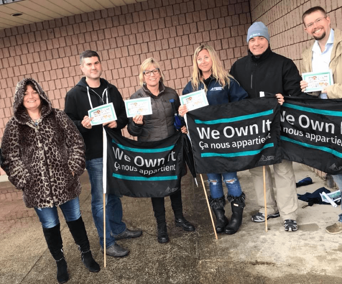 OPSEU members holding We Own It flags rally to save the public LCBO in Orono