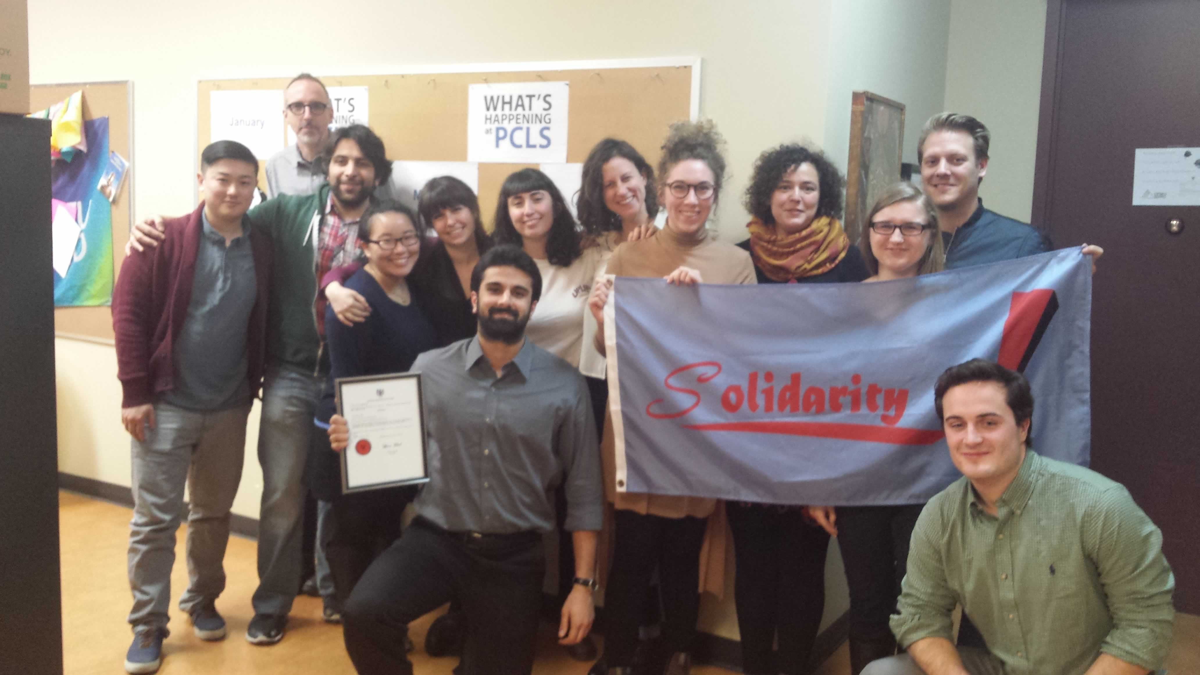 "Summer caseworkers at Parkdale Community Legal Services hold a ""Solidarity!"" banner"