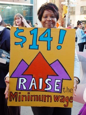 "Woman holds a sign that says ""$14! Raise the minimum wage."""
