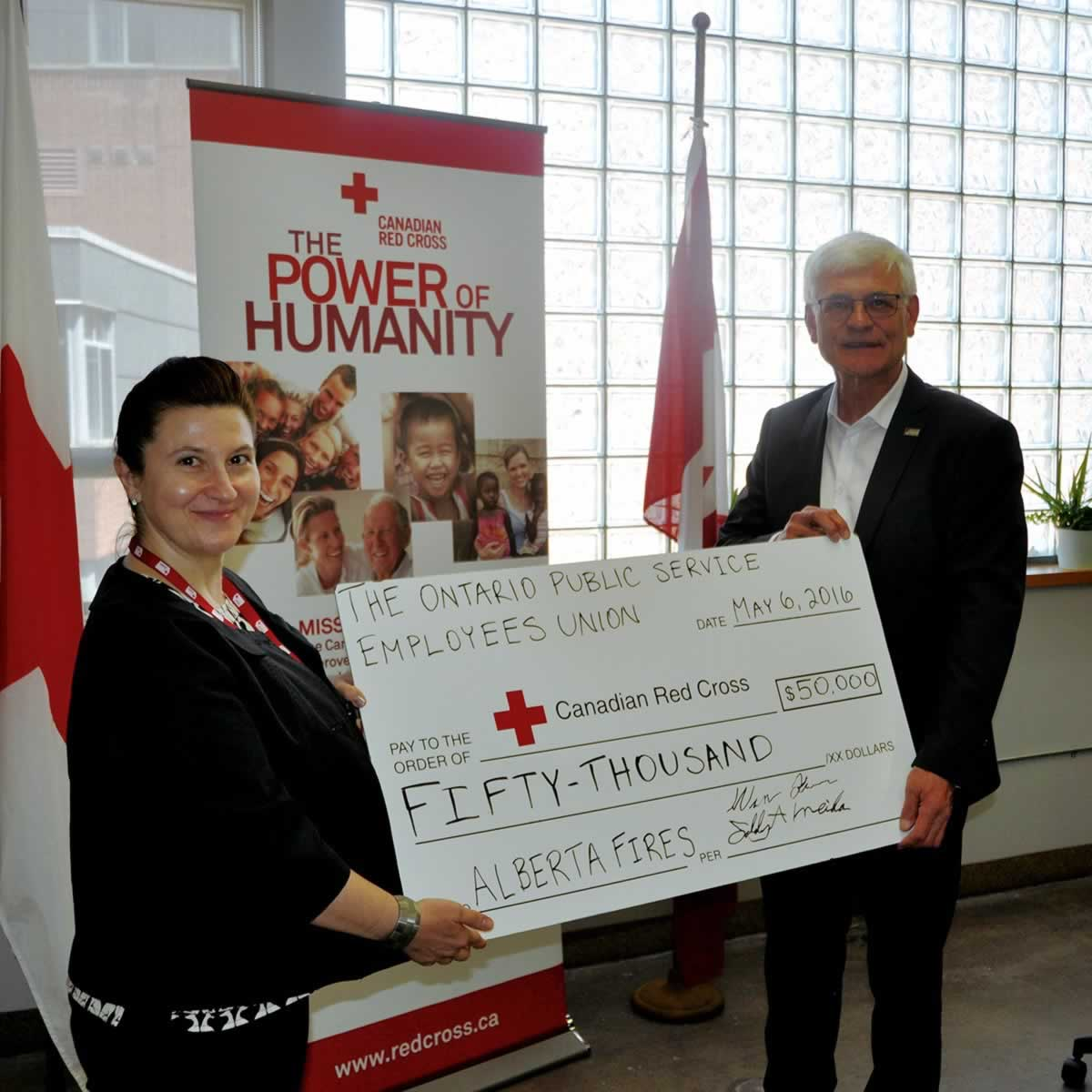 OPSEU member presents a $50,000 cheque to the Canadian Red Cross to help with the Alberta Fires.