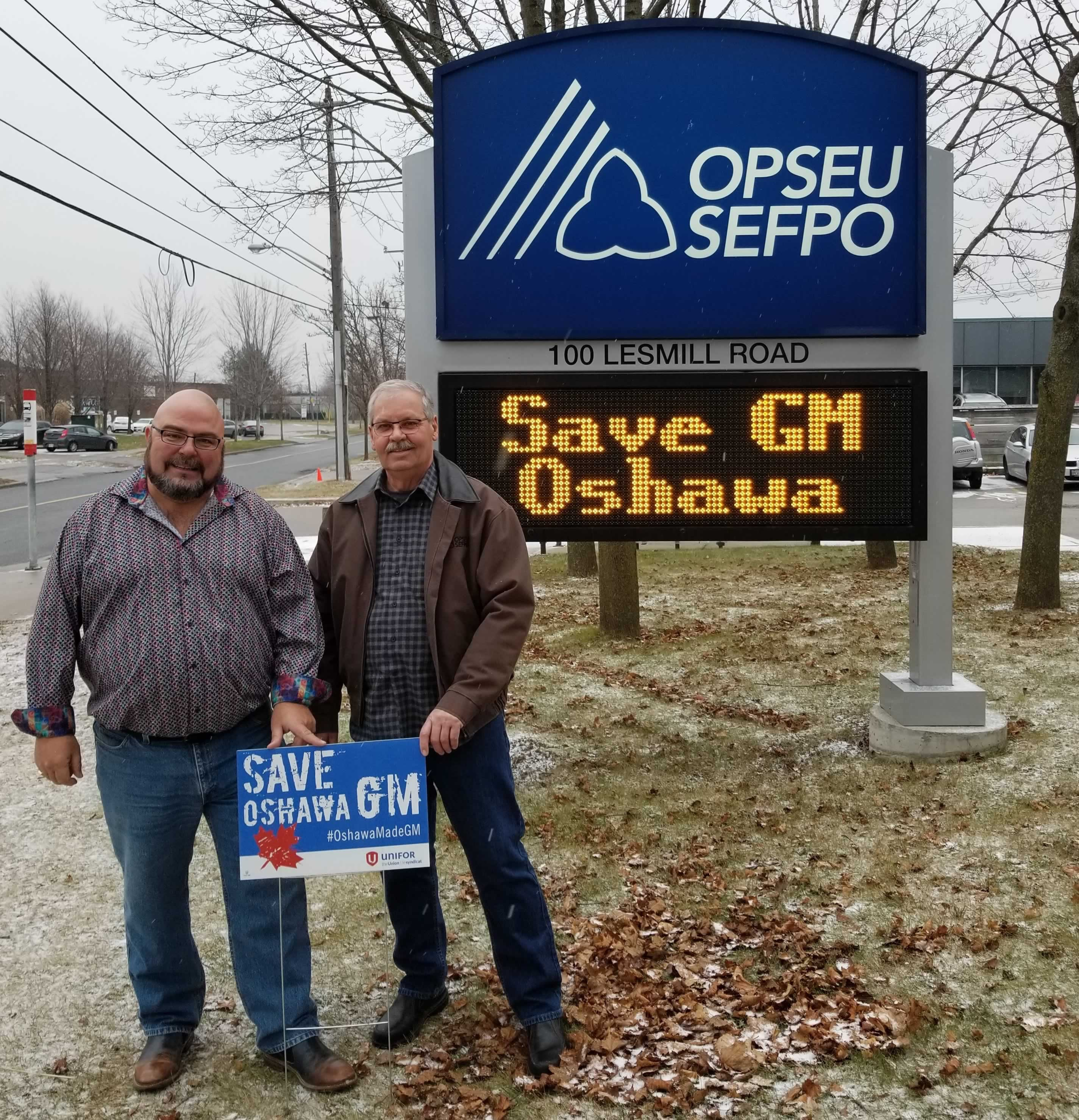 "OPSEU President Warren (Smokey) Thomas and First Vice-President/Treasurer Eduardo (Eddy) Almeida pose outside OPSEU's head office with ""Save Oshawa GM"" signs"