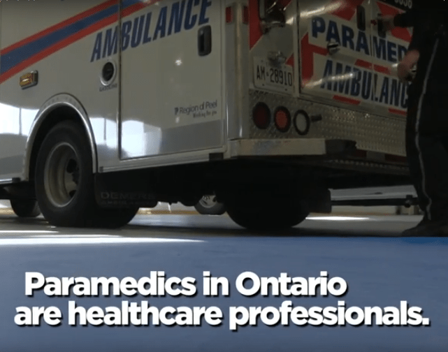 """Ambulance in garage with the caption """"Paramedics in Ontario are healthcare professionals."""""""