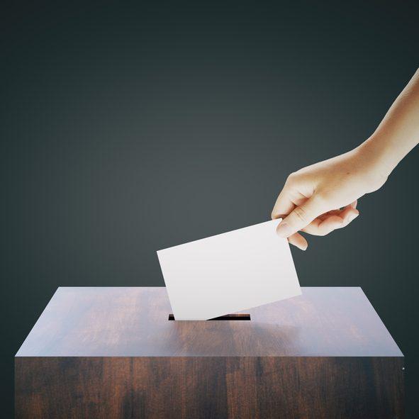 Hand placing ballot into box
