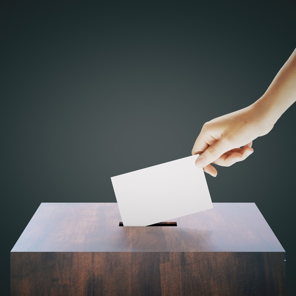 Hand placing ballot into box