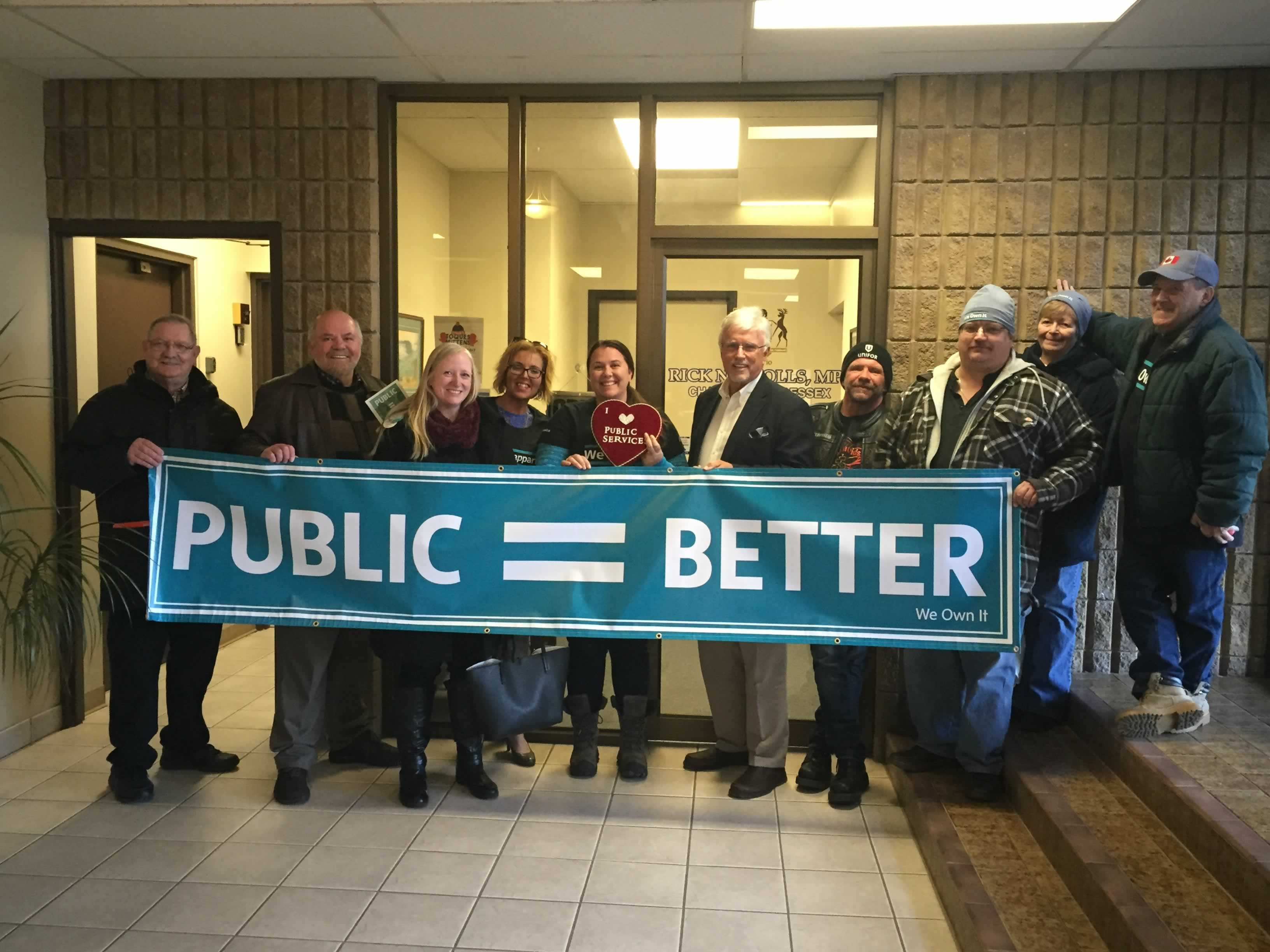 "We Own it campaign supporters hold a ""Public = Better"" banner with Conservative MPP Rick Nicholls"