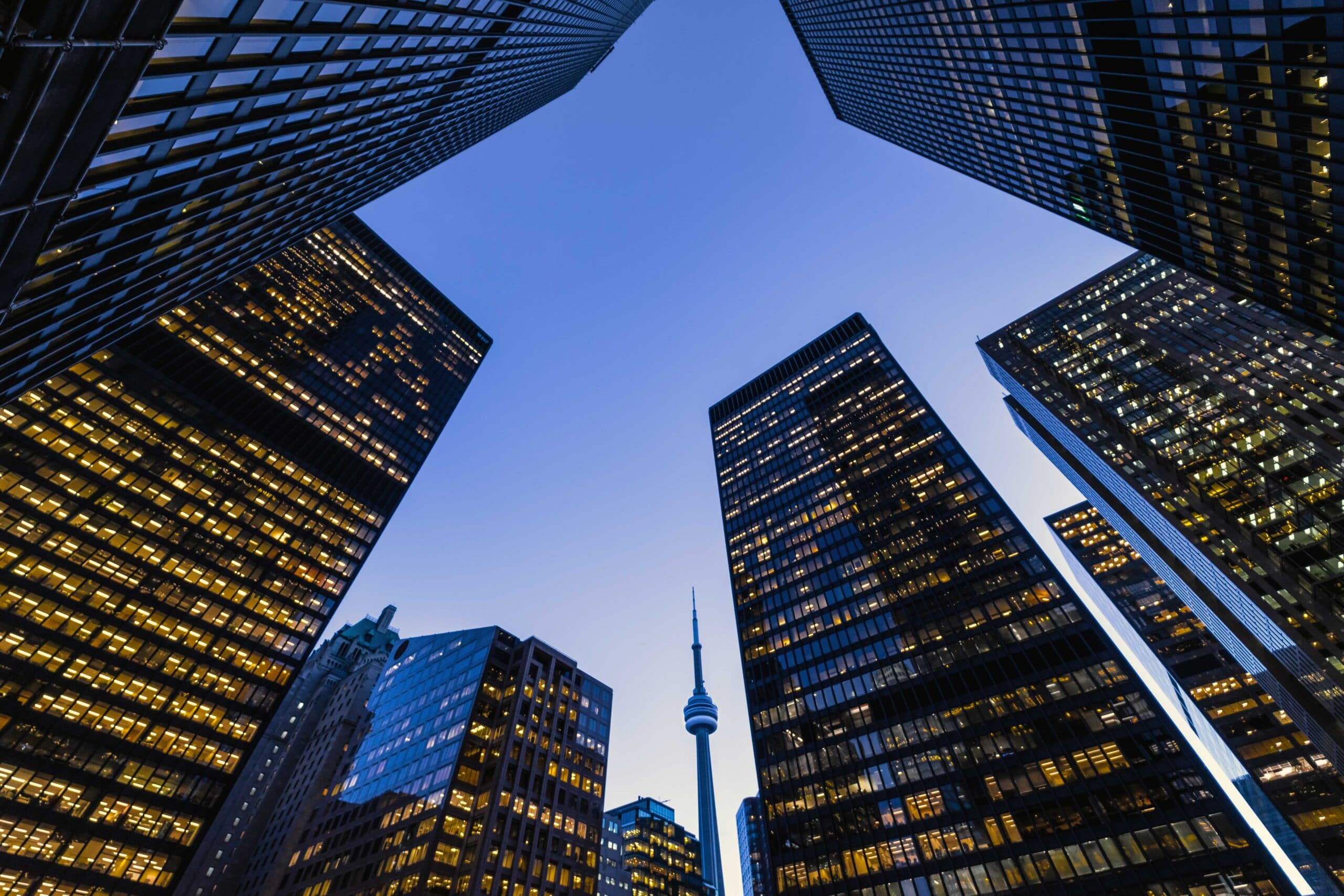 Business district architecture at night in downtown Toronto. Featuring a blue sky and lots of building lights with the famous CN Tower in the background.