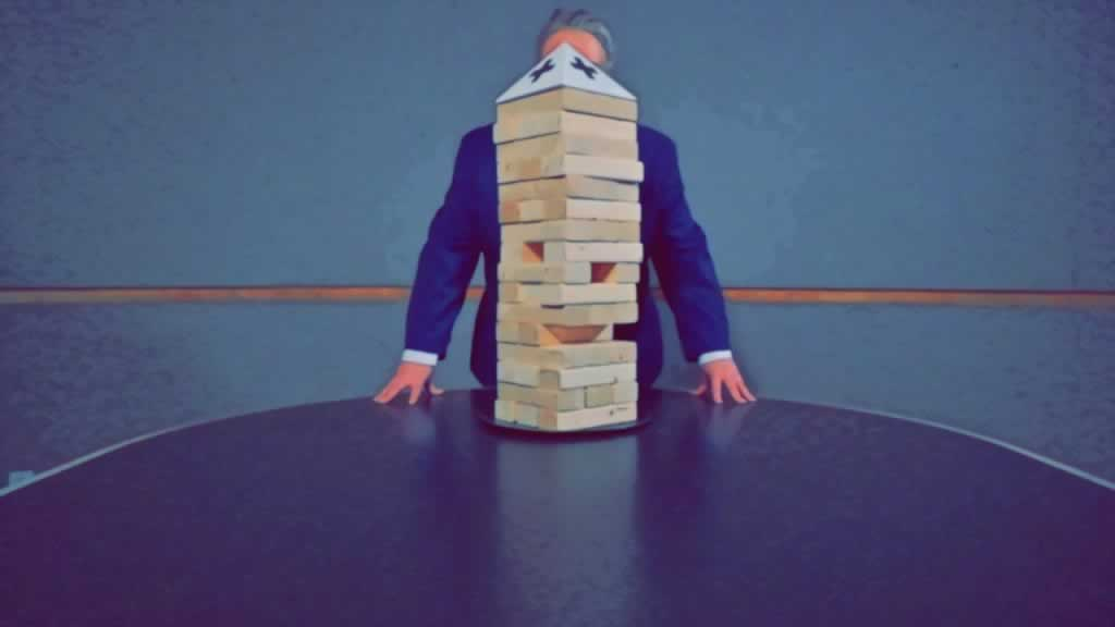 Man standing behind a jenga puzzle