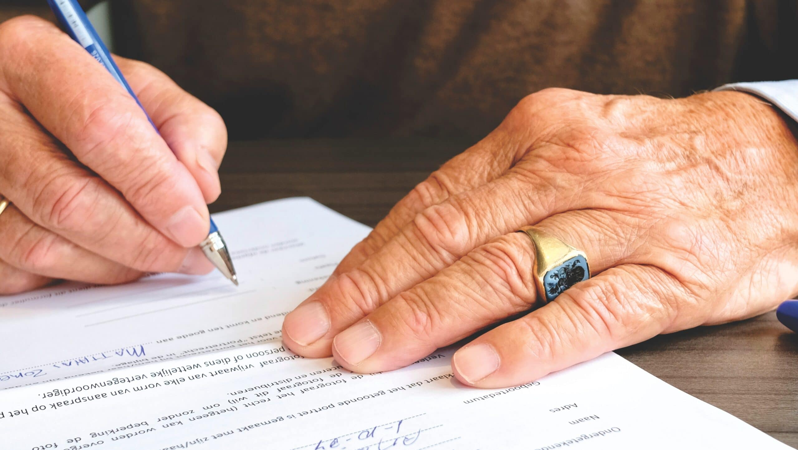 Photo of hands signing a document
