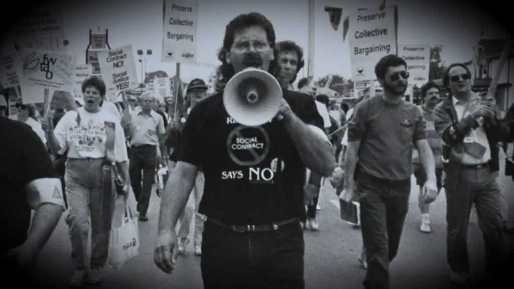 black and white image of protest, people with rally signs Smokey Thomas with a megaphone