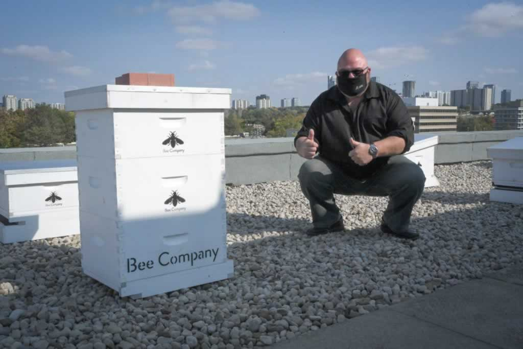 First Vice President Treasurer Eddy Almeida giving a thumbs up next to a bee hive